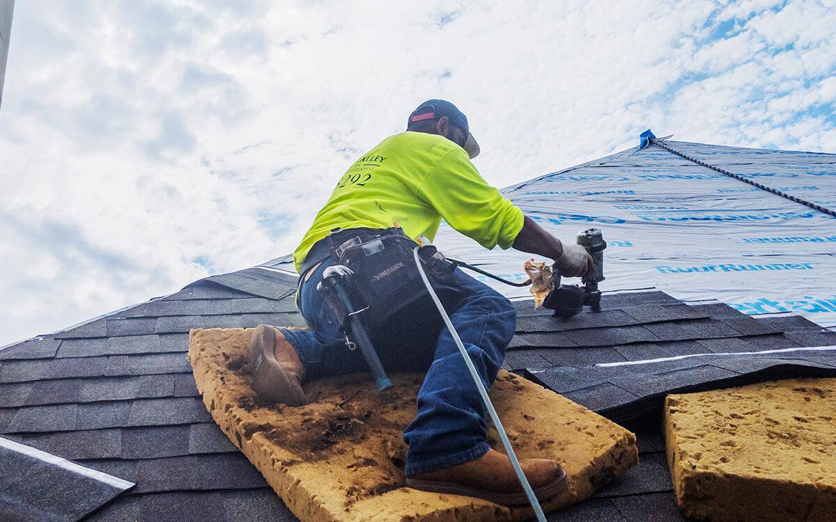 Residential roofer installing shingles on residential building