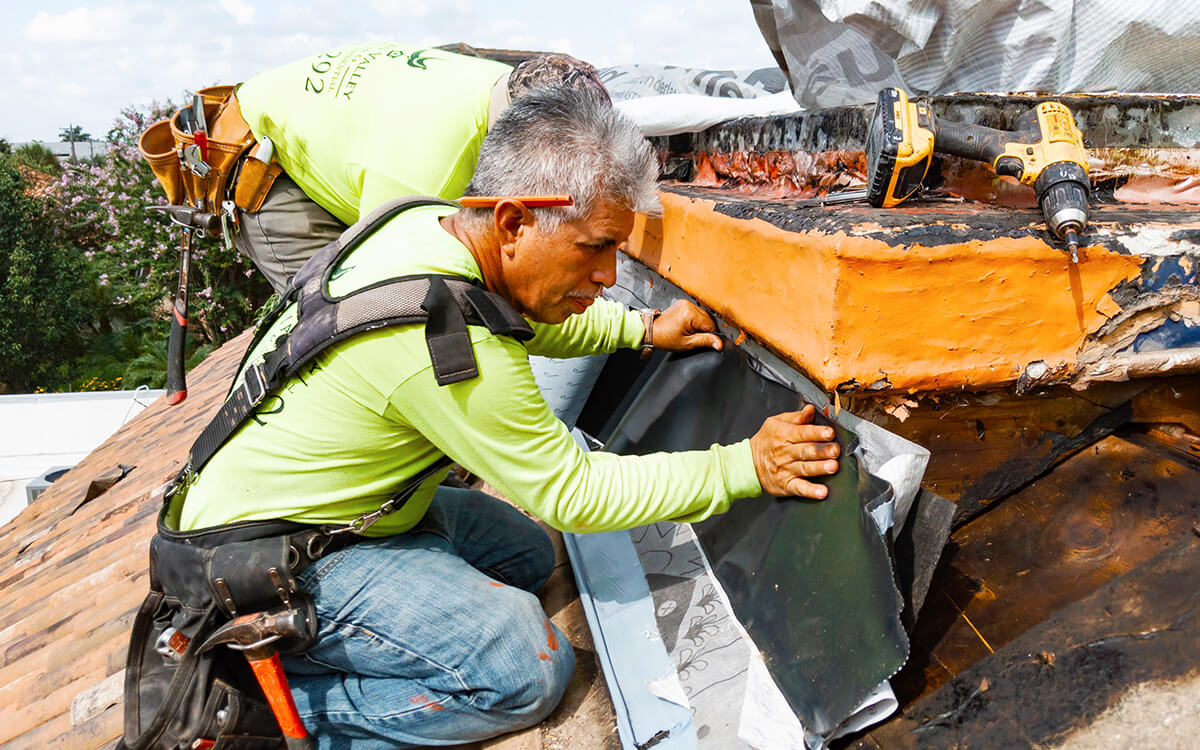 San Antonio roofing contractor repairing a damaged residential tile roof.