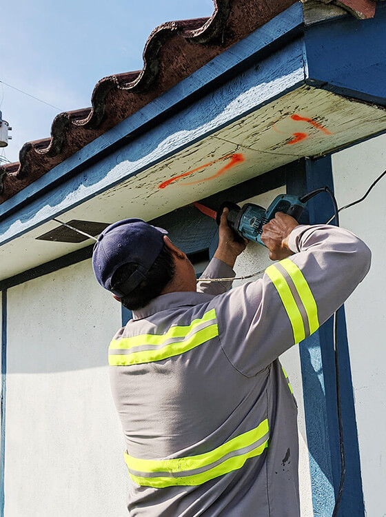 Residential Roofing Repair- McAllen Valley Roofing Co worker repairing wood soffit on a residential home.